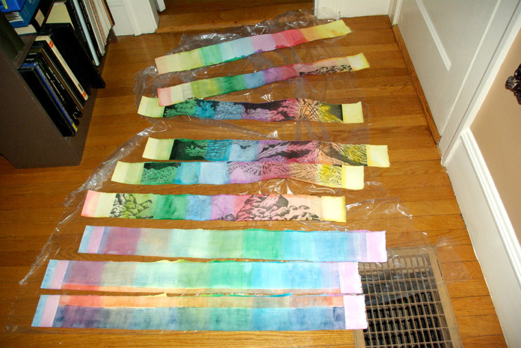 16 Rainbow tinted etching proofs, drying on studio floor.